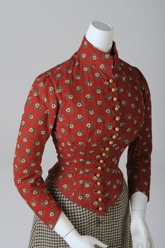"""* Simple Day Dress for Women, around 1890 The colourful, printed bodice and the checkered skirt are a good example for the daily dress of domestic  staff and the working class.  Many sewed their own clothes, even their corsets, or bought second-hand clothing from tailors. A popular place for acquiring such, since 1863, was the """"Tandelmarkt"""", situated between the Bergasse and the Türkenstrasse."""