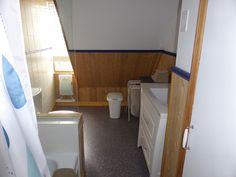 À l'entrée de la salle de bain, une armoire à droite et un bain-douche à gauche. Pour préserver la lumière naturelle, un mur de verre sépare le bain de la cuvette de toilette et donne sur la lucarne faisant face au sud. Un chauffage convecteur avec ventilateur permet de chauffer rapidement la salle de bain. Sous l'évier, on trouve des tiroirs avec un sèche-cheveux et une réserve de papier hygiénique. www.bleulumignon.ca