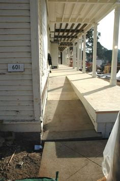 Detail of driveway side of a front deck  with ramp next to house. I would like this deck in poured cement to front door level entrance  so stairs would have to go next to ramp (see other example)- nice white hand rail upstairs and flowing into porch rails right hand side of this picture