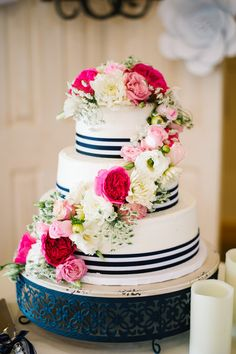 Three-tier cake with blue and white striped ribbon, hot pink, light pink and white cascading flowers {E+E photography}