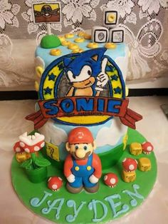Mario and Sonic theme cake. All decorations handmade with fondant. I drew the sonic freehand on icing with edible pen and painted with food colours. www.facebook.com/bouchybakes