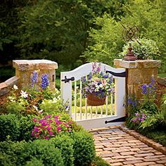 Cottage Garden Gate | For an inviting entrance into a cottage garden, plant a basket with caladiums, angelonias, Madagascar periwinkles, and million bells.