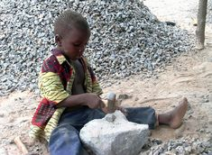 In Focus - World Day Against Child Labor: our-year-old Jacques Monkotan pounds stones in a excavation in Dassa-Zoume, some 200km north of Cotonou, Benin, on February 25, 2007. The children are taken away from school by their parents to work in those excavations and pound stones to be sold by their employers or parents for 30 dollars the barrow. (Fiacre Vidjingninou/AFP/Getty Images)