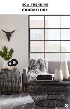 Refresh the look of your living room with this season's favorite duo: Black and White. This simple color palette creates a modern, refined vibe in your space, and lets you add eclectic pieces to the mix, like a mounted steer head and geometric decor, without it feeling cluttered. A combo of materials, like these metal wire tables and ceramic vases, elevate the look. Finish things off and add warmth to the room with a cozy-chic faux-fur throw and some greenery (real or fake).
