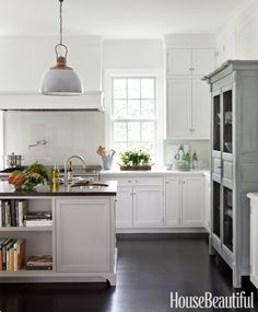 """Designer Samantha Lyman new cabinetry with vintage lights from a Dutch ship, an antique armoire, and a glass backsplash. """"I love classics, but I'm always asking 'What's the twist? What's the cheeky element that gets your attention?' """"   - HouseBeautiful.com"""