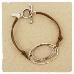 This bracelet features a hammered and oxidized silver ring framed by a thin hammered gold fill ring, suspended from knotted pieces of cotton.