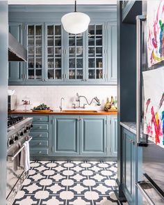 so pretty! Blue kitchen with geometric tile floor and warm butcher block counters @cecebarfieldthompson #beckiowensfeature @allenunruh""