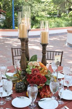 Flowers and tall candleholders with pillar candles
