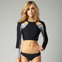 "Long sleeve cropped rashguard with cut out shoulder deatails, halter front design lines, and a circular cut out at center back meant to be worn as a layering piece over swim or the Blazin tank for full coverage.Direct inject Fox head on the left front hem.82/18% Nylon/Elastane.15"" Body Length"
