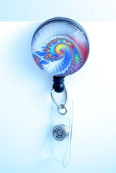 This retractable ID badge reel features a psychedelic swirl design that looks a bit like whipped cream with multiple colors as well. It also makes me think of the surf of the ocean. The badge has a gl