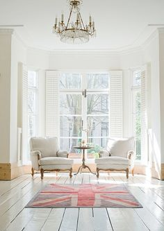 White wood floors, large windows, white theme-colored room with a touch of color from the British flag rug. <>