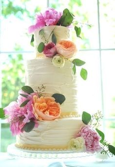 summer flowers cake.  Love the uneven frosting, coupled with the flowers, and different heights of cake layers.