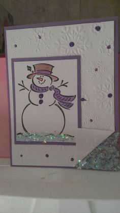 Use your favorite snowman stamp for this handmade Christmas card on a panel color of your choice.  Place that on a large white panel of embossed snowflakes, added to a card base using your chosen color.  Add glitter snow under the snowman and a folded corner of the white panel.