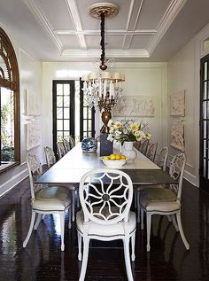 """Darryl's steel-and-concrete dining table is surrounded with hand-painted and -gessoed chairs chosen as a stylistic counterpoint to the table's modern form. The seats, reupholstered with suede cushions, and a Murano glass chandelier complete the mood. """"I had the candle sleeves raised, and the linen shades were custom for the piece,"""" he says."""