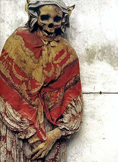 Mummified lady with red shawl. The catacombes of Palermo. ……..SHE ALWAYS SAID SHE WOULDN'T BE CAUGHT DEAD WITHOUT HER FAVORITE RED SHAWL…….WELL, HER FAMILY TOOK IT LITERALLY AND BURIED HER IN IT…….MUST ADMIT, SHE'S A LOVELY CORPSE…………ccp