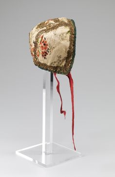 Child's cap, Norway, 1740-1770. Cream silk brocade embroidered with flower bouquets in multicoloured silk threads, metall lace decoration, red silk ribbon binding.