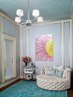 Graphic blue wallpaper is framed in silver for a glamorous backdrop to this ladies' sitting room. A custom round settee with mother-of-pearl buttons and turquoise area rug tie the space together.