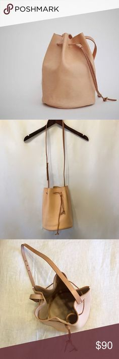HANDMADE Tan Leather Bucket Bag Purse Hello! This bag is brand-new and comes with its original box. Completely handmade from full grain leather. (This means the Leather is currently stiff and will become softer with use!) Only selling because although this bag is absolutely beautiful, I realize I always go back to carrying my larger totes and this purse never gets used. Hoping to find a lovely home for this one!   More details on similar listing on Etsy…