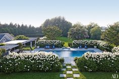 Enhancements made by Juan Montoya Design to a family home in Southampton, New York, include a pergola-topped dining space the firm added to the pool area. The chaise longues, by John Hutton for Sutherland, are cushioned in a Perennials fabric