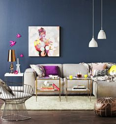 A gorgeous glam and relaxed living room. Navy walls with punches of magenta, brass accents.