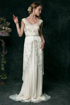 This three layer silk chiffon dress has a wrap-around tea length beaded skirt that exudes pure decadence in antiqued hand beading. With delicate cap sleeves over a sheer sweetheart neckline, this unfo