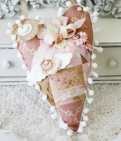 Vintage-style hanging heart patchwork pincushion, handmade from tea-stained fabrics, a crocheted flower, trinket pins, buttons, millinery flowers, pom pom trim, and more