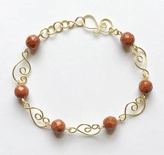 Beautiful wire bracelet with faceted brown goldstone beads, made with gold plate wire. Bracelet is handmade with gold plated designer links and spiral wire clasp. Beads are glass, semi precious beads, faceted beads, round, and very lovely. Wire jewelry, jewelry, gold plate wire, wire,
