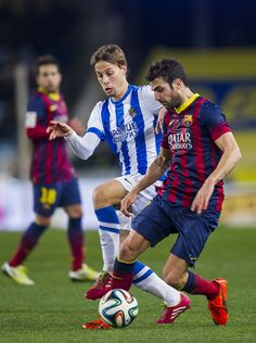 Cesc Fabregas of FC Barcelona duels for the ball with Sergio Canales of Real Sociedad during the Copa del Rey Semi-Final first leg match between Real Sociedad and Barcelona at Estadio Anoeta on February 12, 2014 in San Sebastian, Spain.