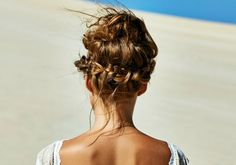 A braided crown underneath a loose bun gives this bridal look a little more dynamism