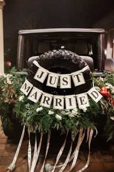 garlands from the church rails are repurposed to dress the couple's jeep! with a just married banner and tin cans tied with ribbon streamers to the back, it is the perfect way to end the reception in a getaway car! Jeep Wedding, Wedding Getaway Car, Our Wedding, Dream Wedding, Just Married Banner, Just Married Car, Newly Married, Bridal Car, Wedding Car Decorations