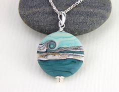 I have a passion for glass in all it´s forms and work both with lampwork, fused and blown glass. This fabulous one of a kind glass bead pendant is part of my lampwork bead range made by me in my little studio in the forest of Sweden. The bead was made from a mix of opaque teal and turquoise glass with a silvered ivory band around it. The bead was slightly etched to make a soft, matt and smooth appearance of the glass.  The pendant has no front or back. You can choose which side you prefer to…