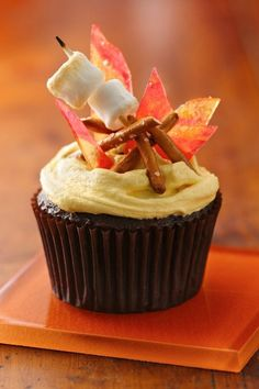 """Holy moly, the recipe for these adorable campfire-inspired cupcakes has been Pinned almost 40,000 times! If you're missing summer camping and bonfires, these chocolaty cupcakes with marshmallow-buttercream frosting will bring back all those good memories. A bundle of pretzel sticks with mini-marshmallows and a candy """"campfire"""" make them almost too cute to eat!"""