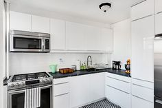 This Clinton Hill co-op kitchen renovation features sleek appliances, modern white lacquered IKEA cabinets, white subway backsplash tiles, and honed black granite countertop to contrast the white tones.