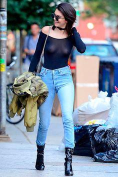 Street style look Kendall Jenner com body transparente, calça jeans e botas preta.