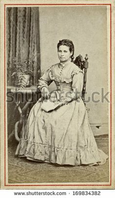 CIRCA 1865 - A vintage Cartes de visite photo of a young pioneer woman. The woman is sitting in a chair with a hoop skirt. A photo from the Victorian Civil War era. A digital copy can be purchased at the above web address.