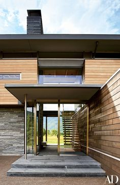 African mahogany siding (upper level), stacked quartzite (left), and red cedar (right) intersect at the main entrance; Pietra del Cardoso sandstone paves the porch and foyer.