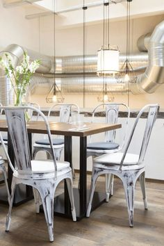 Industrial chairs and taylor made industrial tables. Ay Illuminate hanging lamps.