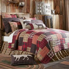 The Wyatt quilt bedding collection is a patchwork block quilt in rustic lodge colors of khaki, crimson, black, and moss green plaid fabric. Pillows with a fox, bear and dear accent the bedding set.
