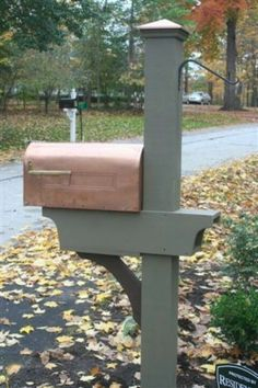 Mailbox Makeover idea, I like the place for the paper, the hook on the back for a plant and you could hang a solar powered lantern above the mailbox or on top of the pole.