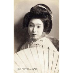 1920's. Japanese Woman with Parasol. An almost melancholic image of a young Japanese woman with a traditional Japanese hairstyle holding a paper parasol. During the early 20th century, picture postcards of bijin (beautiful women) were extremely popular in Japan