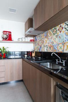 Cozinha com do ladrilho hidráulico, dando o charme e a cor para o neutro da  bancada preta, o porcelanato cinza e os móveis em tom de madeira