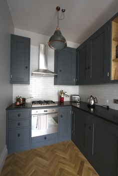Sustainable Kitchens - Industrial Kitchen in Bath. Oak shaker style kitchen painted with Farrow & Ball Down Pipe. White metro tiles with stainless steel Smeg oven and hood. Parquet tiled flooring in herringbone pattern and hanging maritime pendant light complete this stylish kitchen. The sleek premium black honed granite contrasts nicely with the white metro tiles throughout. The high ceilings have been utilised to create narrow and tall units for extra storage in this small apartment…