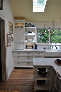 Open shelving by sink makes the window feel more open. Interesting roll top cupboards.