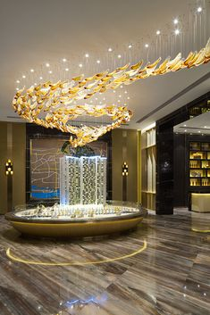 The reception area of Jiu Zhou Ju Residence Guangzhou features a lighting  sculpture aptly named River of Gold 7fdd0665c6