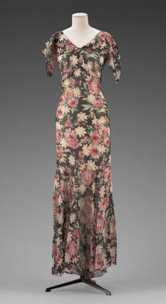 American, early 1930s. Woman's bias-cut chiffon dress printed with overall pattern of black, yellow, green, and red flowers, cape-like double layer at neckline, and cap sleeves.