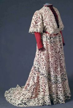 Venetian needle lace gown with large floral motifs and decorative straps with mesh and bars. Bodice with high, round neck, open center. Short, wide sleeves. Long, bell-shaped skirt with train. Mode Museum, Antwerp