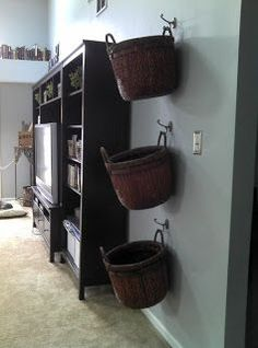 Brilliant and pretty! Baskets from hobby/craft store and hooks from Walmart! Removable storage for gathering blankets, remotes, clutter...then hang back up!
