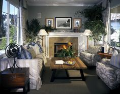 Small living room with windows on either side. Enclosed fireplace flanked by matching lamps and houseplants. Various blue and cream patterned sofa and chairs.