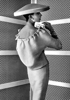 1955, gray linen two-piece, the top is deeply-cut in the back with ribbon that is gathered and fastened in bows, by Balenciaga
