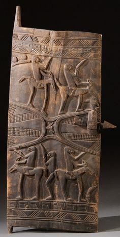 Large, carved African tribal wood grainary door panel with four equestrian figures